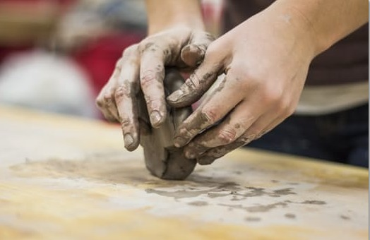 Hands of a person working with clay